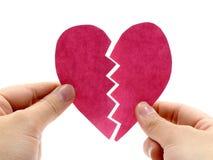 Corazón rosado quebrado en la mano Fotos de archivo
