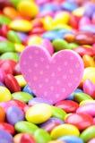 Corazón rosado y sabelotodos coloridos del chocolate Foto de archivo
