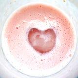 Corazón sobre el vidrio rosado del batido de leche Imagen de archivo libre de regalías