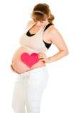 Corazón sonriente de la explotación agrícola de la mujer embarazada cerca de la panza Imagen de archivo libre de regalías