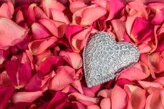 Corazón tallado decorativo en el fondo rojo de pétalos color de rosa imagenes de archivo