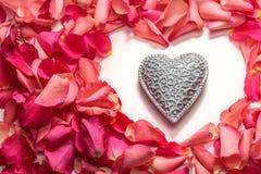 Corazón tallado decorativo en la forma del corazón de pétalos color de rosa rojos foto de archivo libre de regalías