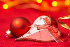 Corazón y bolas de la Navidad en fondo rojo Fotografía de archivo libre de regalías