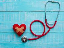 Corazón y estetoscopio rojos en fondo de madera brillante azul cure imagen de archivo libre de regalías