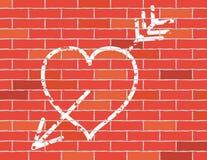 Corazón y flecha en la pared de ladrillo. Fotografía de archivo libre de regalías