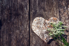 Corazón y flor blanca de madera tallados en un fondo del verraco viejo Fotos de archivo libres de regalías