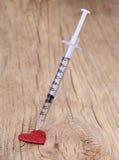 Corazón y jeringuilla rojos del brillo con la droga sobre de madera Foto de archivo libre de regalías