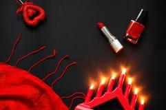 Corazón y lápiz labial rojos, en un fondo negro, una cadena de perlas blancas y un pañuelo de seda Imágenes de archivo libres de regalías