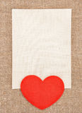 Corazón y lona rojos sentidos en la arpillera Imagen de archivo libre de regalías