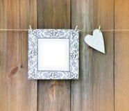 Corazón y marco en el fondo de madera Foto de archivo libre de regalías