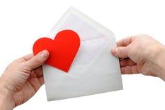 Corazón y sobre de la tarjeta del día de San Valentín en manos Imagen de archivo