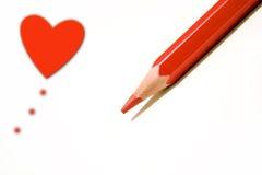 Corazón y una pluma roja Imagen de archivo libre de regalías