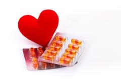 Corazón y vitamina rojos en cápsulas Imagen de archivo libre de regalías