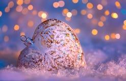 Coraz?n de cristal en una nieve y fondo borroso entonado del color del bokeh que brilla con las luces que brillan intensamente De imagen de archivo libre de regalías