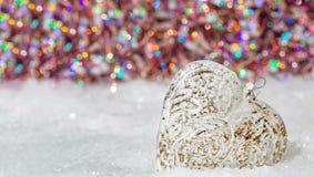 Coraz?n de cristal en una nieve y fondo borroso entonado del color del bokeh que brilla con las luces que brillan intensamente De foto de archivo