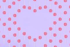 Coraz?n hecho fuera de los caramelos del lollypop en el fondo rosado, espacio de la copia Concepto dulce de la ni?ez foto de archivo libre de regalías