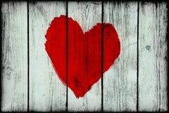 Corazón abstracto brillante rojo en la pared de madera vieja del grunge Imagen de archivo