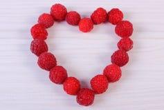 Corazón de frambuesas frescas en la tabla de madera blanca, símbolo del amor Fotos de archivo libres de regalías