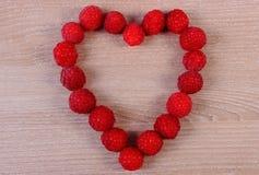 Corazón de frambuesas frescas en la tabla de madera, símbolo del amor Fotos de archivo libres de regalías