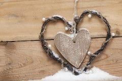 Corazón de madera con los perls en nieve Foto de archivo