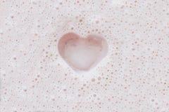 Corazón en espuma rosada del batido de leche Fotos de archivo libres de regalías