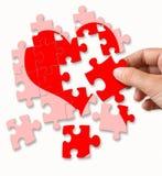 Corazón quebrado rojo hecho por los pedazos del rompecabezas Foto de archivo
