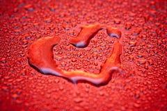 Corazón rojo en gotas del agua Fotos de archivo
