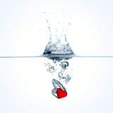 Corazón rojo que cae en el agua Fotos de archivo