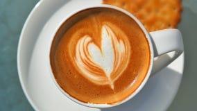 Corazoncaffee, mit Untertasse Im Milchkaffeeschaum wurde Kaffeeschaum kunstvoll ein Herz beschworen stockfoto