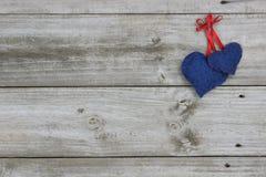 Corazones azules del calicó que cuelgan en el fondo de madera Fotos de archivo libres de regalías
