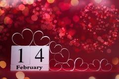 Corazones blancos y calendario de bloque de madera en fondo rojo Tarjeta del día de tarjetas del día de San Valentín copie el esp fotografía de archivo