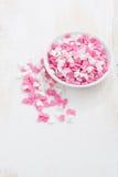 corazones coloreados del azúcar en un cuenco blanco en la tabla de madera blanca Fotografía de archivo libre de regalías