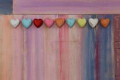 Corazones coloridos del amor en tablero pintado Foto de archivo