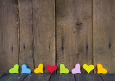 Corazones coloridos en el fondo de madera para una tarjeta de felicitación. Imagen de archivo libre de regalías
