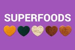 Corazones con la cúrcuma, el spirulina, los polvos de cacao, la harina de la almendra y el azúcar de la palma de coco Bio Superfo fotos de archivo