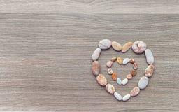 Corazones de guijarros multicolores en superficie de madera Un insi del corazón Imagen de archivo