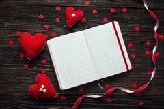 Corazones de la tarjeta del día de San Valentín con el cuaderno en blanco abierto en backgro de madera oscuro Imágenes de archivo libres de regalías