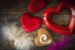 Corazones de la tarjeta del día de San Valentín de diversos materiales en una parte posterior de madera del vintage Fotos de archivo