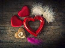 Corazones de la tarjeta del día de San Valentín de diversos materiales en una parte posterior de madera del vintage Fotos de archivo libres de regalías