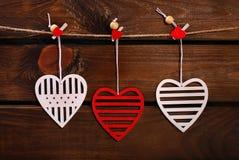 Corazones de la tarjeta del día de San Valentín que cuelgan en fondo de madera Fotografía de archivo
