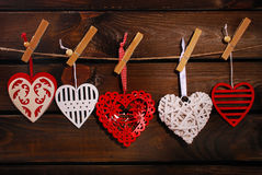 Corazones de la tarjeta del día de San Valentín que cuelgan en fondo de madera Foto de archivo libre de regalías