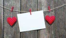 Corazones de la tela, tarjeta en blanco y pared de madera Fotografía de archivo libre de regalías