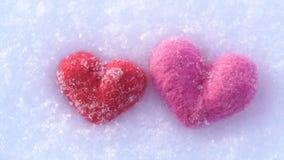 Corazones de lana rojos y rosados en la nieve blanca en invierno almacen de video
