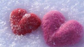 Corazones de lana rojos y rosados en la nieve blanca en invierno metrajes