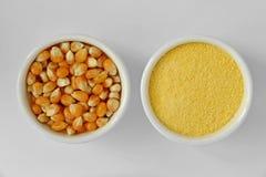 Corazones de maíz y harina de maíz secos en cuenco en el fondo blanco Imágenes de archivo libres de regalías