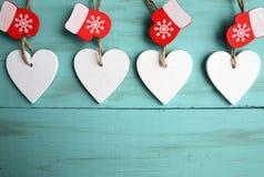 Corazones de madera blancos decorativos de la Navidad y manoplas rojas en fondo de madera azul con el espacio de la copia Foto de archivo