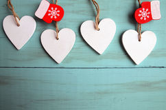 Corazones de madera blancos decorativos de la Navidad y manoplas rojas en fondo de madera azul con el espacio de la copia Imagen de archivo libre de regalías