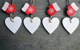 Corazones de madera blancos decorativos de la Navidad y manoplas rojas en fondo de madera rústico gris con el espacio de la copia Imagenes de archivo