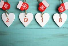 Corazones de madera blancos decorativos de la Navidad y manoplas rojas con 2018 números en fondo de madera azul con el espacio de Imagenes de archivo