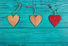 Corazones de madera en un fondo azul Colgantes hechos de la madera bajo la forma de corazón Visión superior Imagen de archivo libre de regalías
